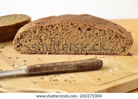 Homemade olive rye bread with flax seeds on a wooden board - stock photo