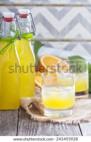 Homemade orange liqueur with fresh oranges on table - stock photo