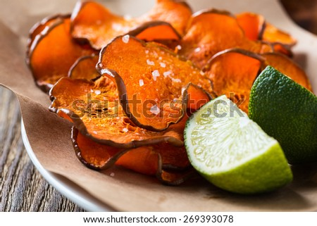 Homemade organic baked pumpkin chips served with lime wedges on kraft paper - stock photo