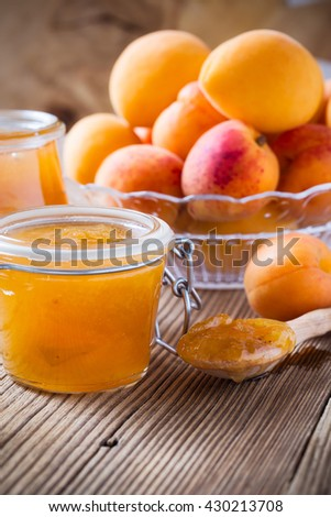 Homemade organic jam in glass jar and ripe apricots on  wooden rustic table - stock photo
