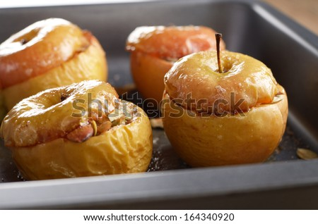 Homemade oven baked apples stuffed with pumpkin seeds and almond nuts in baking pan closeup