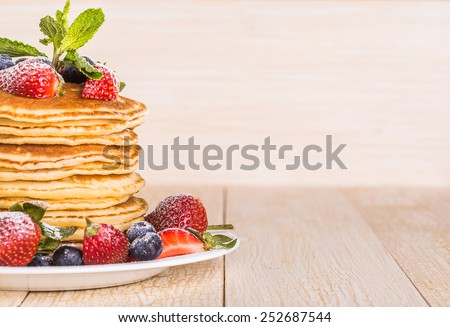 Homemade pancakes with berries and fruit on a white background - stock photo