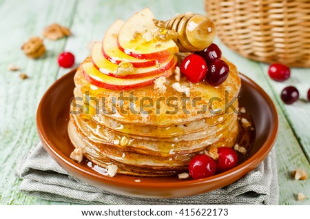 Homemade pancakes with honey, apple, cranberries and nuts. A stack of pancakes on a wooden table