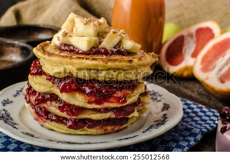Homemade pancakes with jam and bananas with chocolate on top, grapefruit juice - stock photo