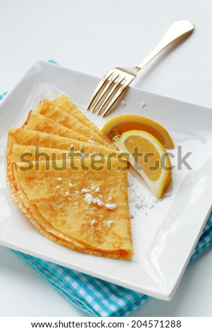 Homemade pancakes with lemon garnish and dusted with sugar