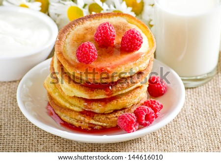 Homemade pancakes with raspberry jam on the daisies background