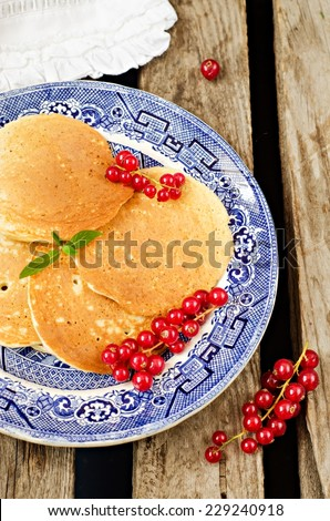 Homemade pancakes with redcurrants in vintage plate on wooden background