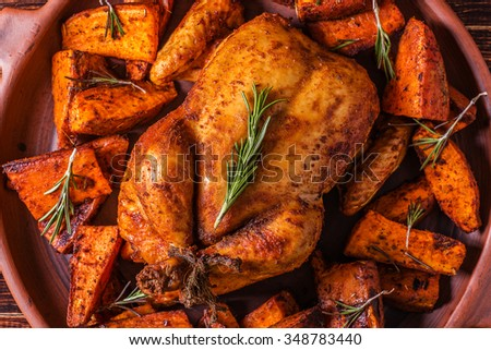 Homemade Paprika and Herb Whole Chicken with spices Sweet Potato on dark background. - stock photo