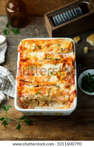 Homemade pasta bake with cheese, pesto and tomato sauce