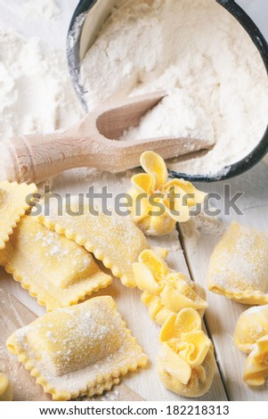 Homemade pasta ravioli and perle on wooden table with metal mug of flour