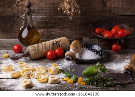 Homemade pasta ravioli on old wooden table with flour, basil, tomatoes, olive oil and vintage kitchen accessories - stock photo