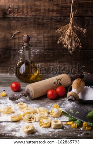 Homemade pasta ravioli on old wooden table with flour, basil, tomatoes, olive oil and vintage kitchen accessories. See series
