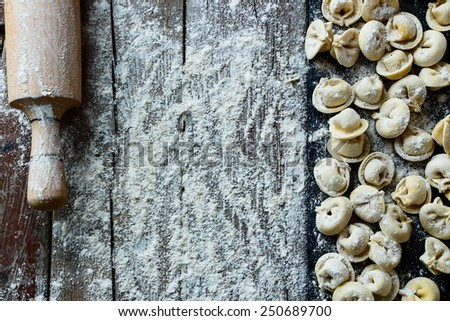 Homemade pasta ravioli over rustic wooden table with roller. Top view. - stock photo