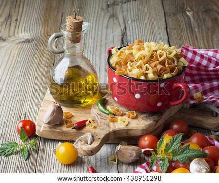 Homemade pasta. Traditional pasta in the form of hearts in a red ceramic pot before cooking surrounded by bright colored cherry tomatoes, hot peppers, oregano, with a jug of olive oil - stock photo