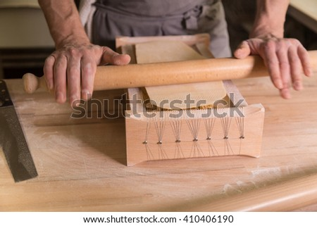 Homemade pasta with rolling pin on a wooden table