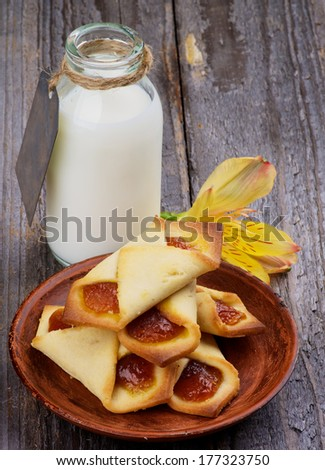 Homemade Pastry Jam Wrapped and Bottle of Milk Decorated with Yellow Flower isolated on Rustic Wooden background - stock photo