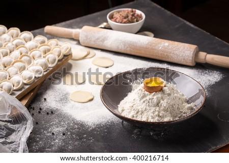 Homemade pelmeni with ingredients on black background - stock photo