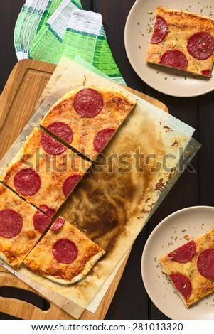 Homemade pepperoni or salami pizza cut in pieces on baking paper on wooden board and served on plates on the side, photographed overhead on dark wood with natural light - stock photo