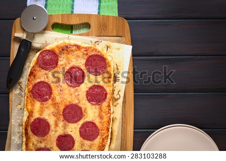 Homemade pepperoni or salami pizza on baking paper with pizza cutter on wooden board, photographed overhead on dark wood with natural light - stock photo