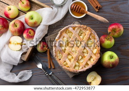 Homemade pie with apples, spices and cinnamon on dark rustic wooden background, selective focus