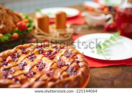Homemade pie with cowberry jam on festive table - stock photo