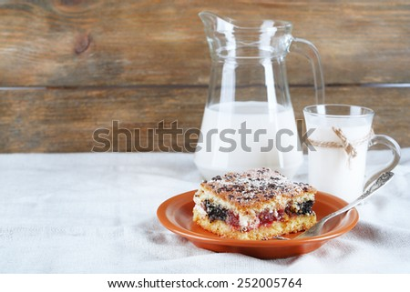 Homemade pie with jam and glass and jug of milk on white tablecloth and wooden planks background - stock photo