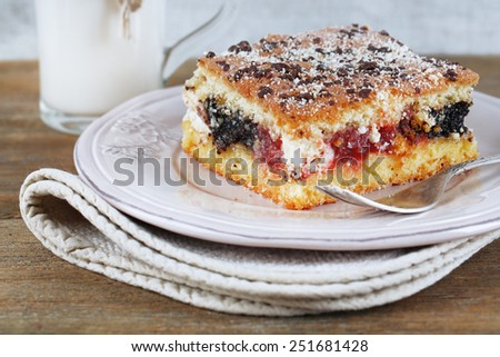 Homemade pie with jam and glass of milk on wooden table and light cloth background - stock photo