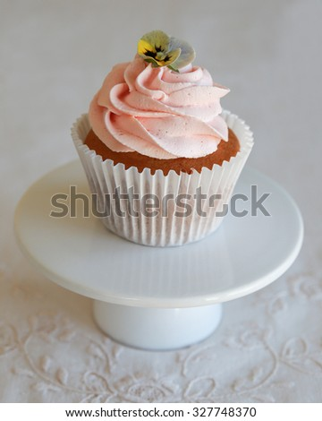 Homemade pink frosting vanilla cupcakes with edible flowers on cake stand - stock photo