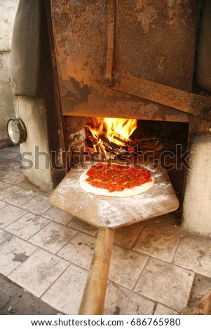 homemade pizza entering woodfired oven stock photo royalty free