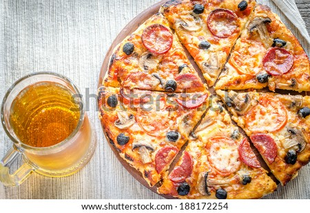 Homemade pizza with a glass of beer - stock photo