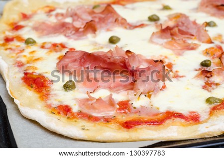 homemade pizza with cooked ham, capers,mozzarella and tomato sauce