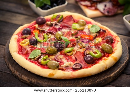 Homemade pizza with ham, cheese, vegetables and pizza ingredients on the table - stock photo
