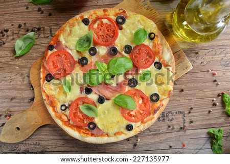Homemade pizza with prosciutto, mozzarella, tomatoes and black olives