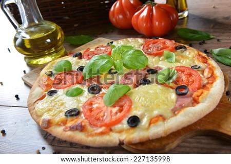 Homemade pizza with prosciutto, mozzarella, tomatoes and black olives - stock photo