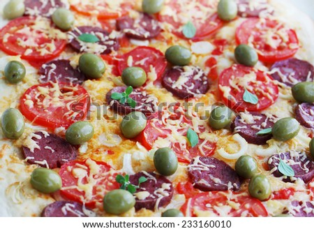 homemade pizza with sausage, olives and oregano - stock photo