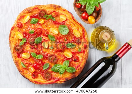 Homemade pizza with tomatoes, mozzarella and basil. Top view on wooden table