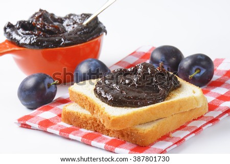 Homemade plum jam on a slice of bread - stock photo