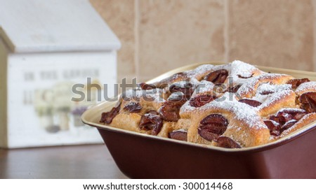 Homemade plum pie in a baking dish. Rustic style. - stock photo