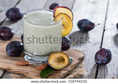 Homemade Plum Smoothie on vintage wooden background - stock photo