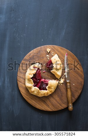 Homemade pluot pie on the wooden cutting board. Chalkboard background with copy space - stock photo