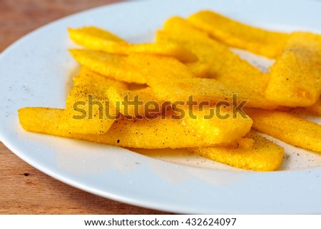 Homemade polenta chips on a white plate