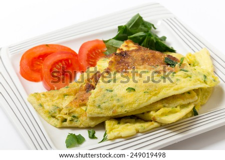 Homemade potato and parmesan cheese frittata omelet, with tomato and rocket, from an Italian recipe - stock photo