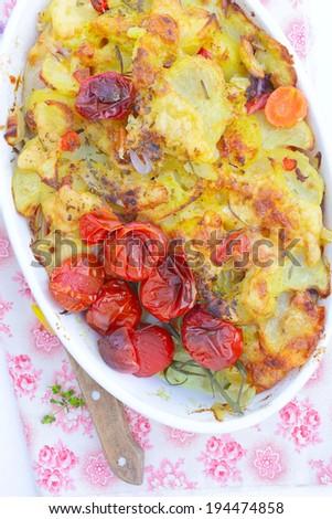 Homemade potato casserole with roasted tomatoes. - stock photo