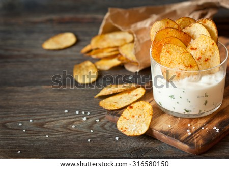 Homemade potato chips and spicy dip served in glass. - stock photo