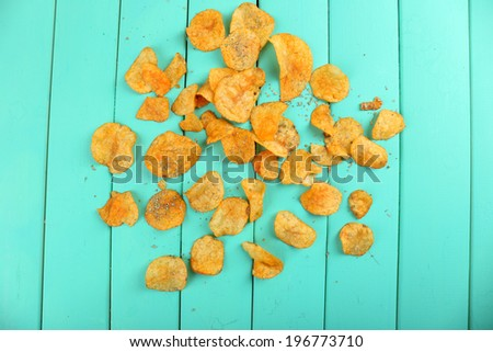 Homemade potato chips on color wooden table - stock photo