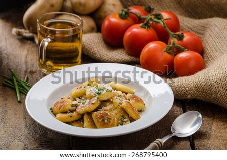 Homemade potato gnocchi with nuts and parmesan cheese, fresh herb chive sprinkled on top, czech beer drink - stock photo
