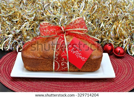 Homemade pound cake decorated with a red Christmas Ribbon and Merry Christmas card in front of gold tinsel. - stock photo