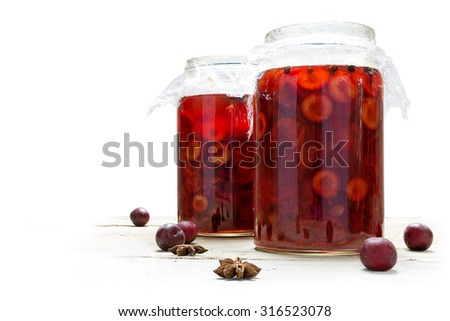 Homemade preserved red fruits with spices in two glass jars, isolated against a white background - stock photo
