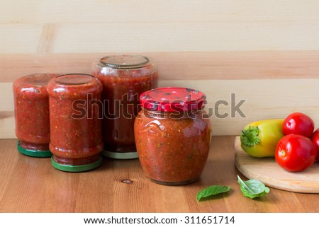 Homemade preserved tomato sauce with bell pepper, basil and oregano in a glass jar on wooden table - stock photo