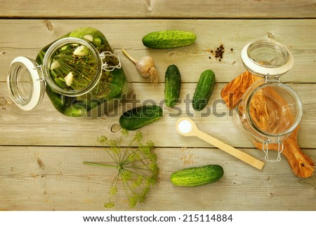 Homemade preserves. Preparation of pickled cucumbers. Fresh cucumbers in the jar and ingredients on the table - stock photo